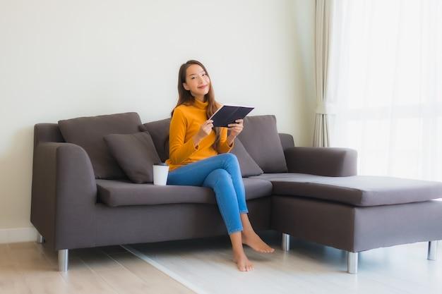 Giovane libro di lettura asiatico della donna sul sofà Foto Gratuite