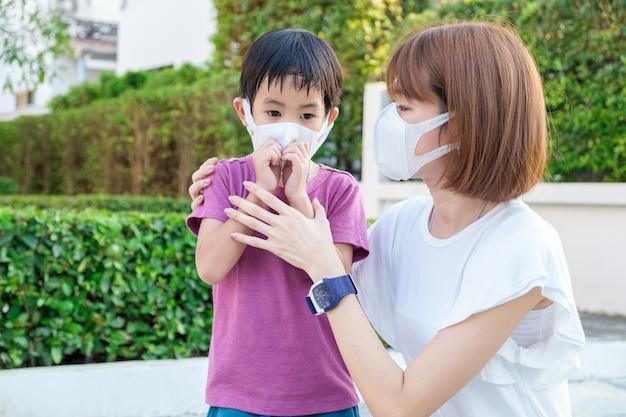 Giovane madre asiatica che indossa la maschera protettiva pm2.5 per suo figlio al parco all'aperto Foto Premium