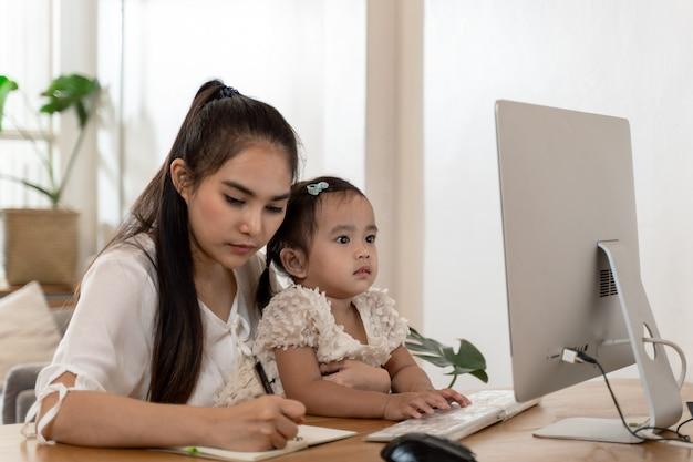 Giovane madre asiatica che lavora dalla casa e che tiene bambino Foto Premium