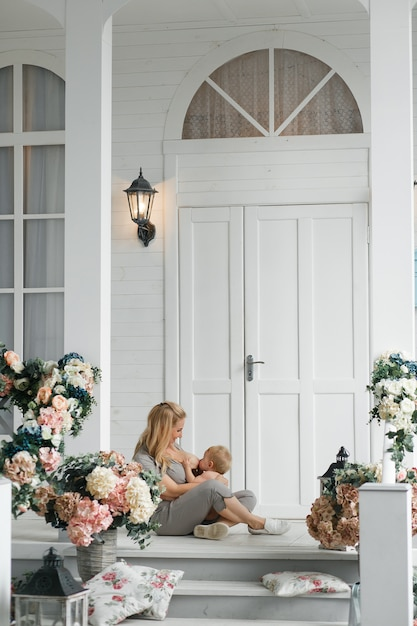 Giovane madre che allatta al seno bambino, seduto sul pavimento vicino a casa veranda all'aperto. Foto Gratuite