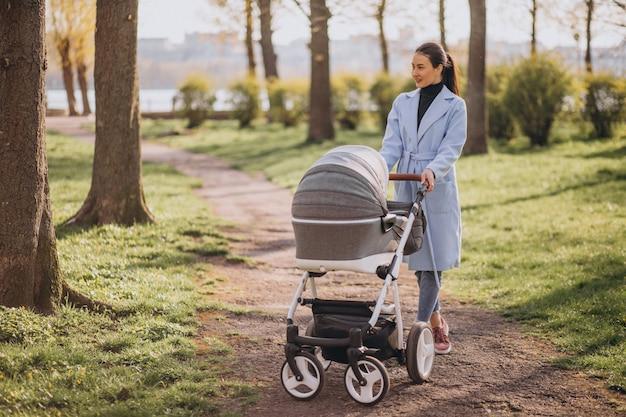 Giovane madre che cammina con carrozzina nel parco Foto Gratuite