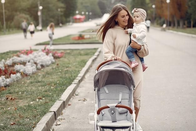 Giovane madre che cammina in un parco di autunno con il trasporto Foto Gratuite
