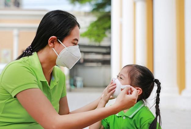 Giovane madre che indossa una maschera protettiva per sua figlia Foto Premium