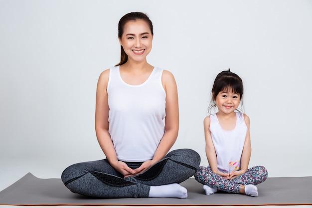 Giovane madre che prepara figlia adorabile con yoga Foto Gratuite