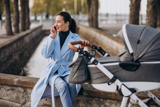 Giovane madre che si siede con carrozzina nel parco Foto Gratuite