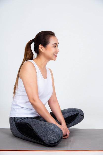 Giovane madre che si siede sul cuscinetto di yoga per l'esercizio Foto Gratuite