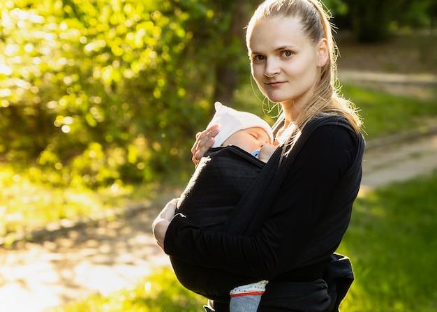 Giovane madre che trasporta un neonato sleepimg bambino. Foto Premium