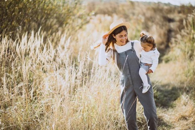 Giovane madre con la sua piccola figlia in un campo di autunno Foto Gratuite