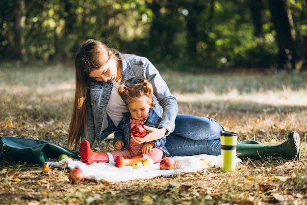 Giovane madre con la sua piccola figlia in un parco di autunno che ha picnic Foto Gratuite