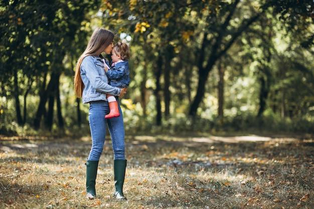 Giovane madre con la sua piccola figlia in un parco di autunno Foto Gratuite