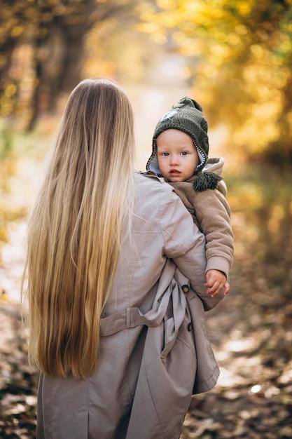 Giovane madre con la sua piccola figlia in un parco in autunno Foto Gratuite