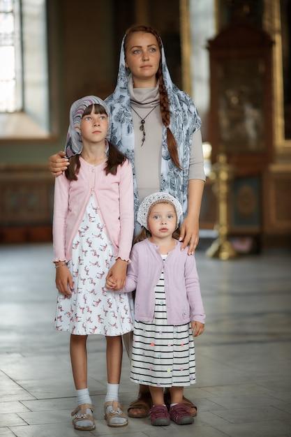 Giovane madre e la sua piccola figlia caucasica bionda con le candele in chiesa russa ortodossa Foto Premium