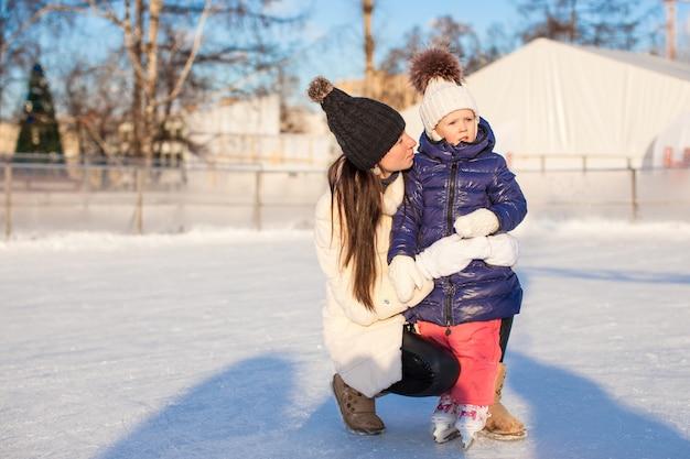 Giovane madre e la sua piccola figlia sveglia su una pista di pattinaggio Foto Premium