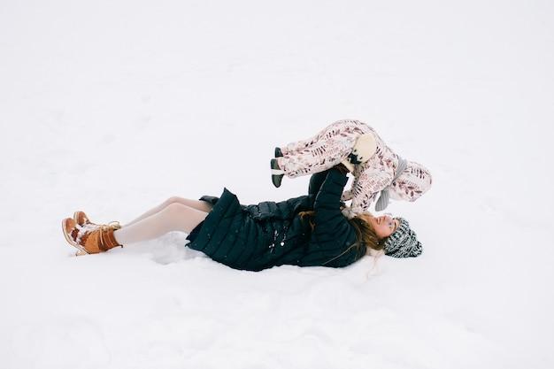 Giovane madre felice che gioca con il suo bambino adorabile nel campo nevoso di inverno. Foto Premium
