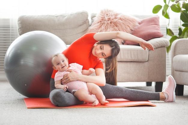 Giovane madre graziosa che risolve con il suo piccolo bambino a casa Foto Premium