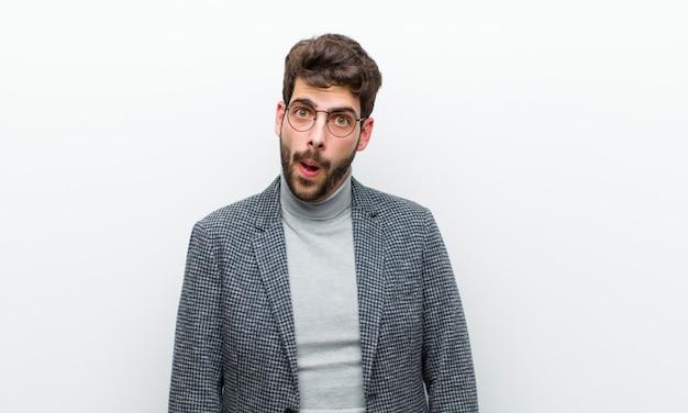 Giovane manager che si sente perplesso e confuso, con un'espressione stupida e sbalordita guardando qualcosa di inaspettato contro il muro bianco Foto Premium