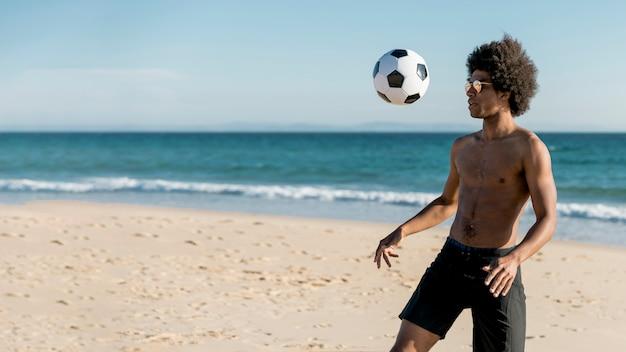 Giovane maschio afroamericano che gioca a calcio sulla spiaggia Foto Gratuite