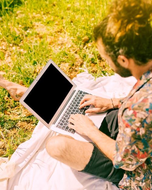 Giovane maschio barbuto che fissa al computer portatile in radura Foto Gratuite