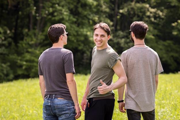 Giovane maschio che fa segno eccellente con gli amici che stanno indietro nel prato Foto Gratuite