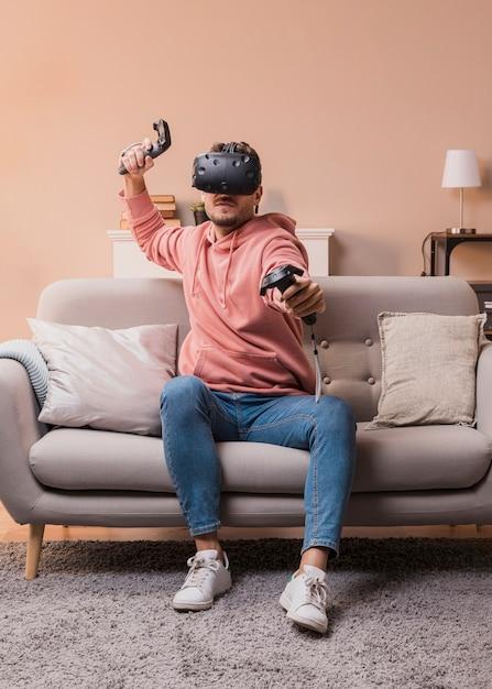 Giovane maschio che gioca con l'auricolare virtuale Foto Gratuite