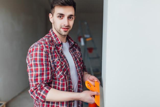 Giovane maschio grazioso con la spatola sulle mani, facendo le riparazioni Foto Premium
