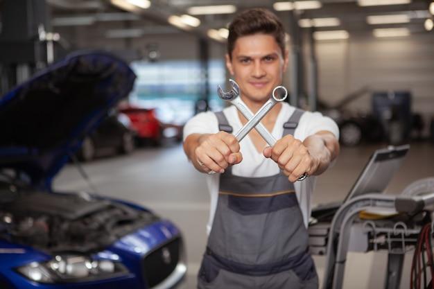 Giovane meccanico di automobile bello che ripara veicolo nel suo garage Foto Premium