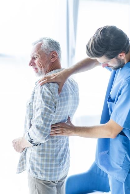 Giovane medico che esamina facente male indietro dell'uomo anziano Foto Gratuite