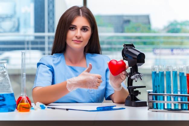 Giovane medico con cuore rosso in laboratorio Foto Premium