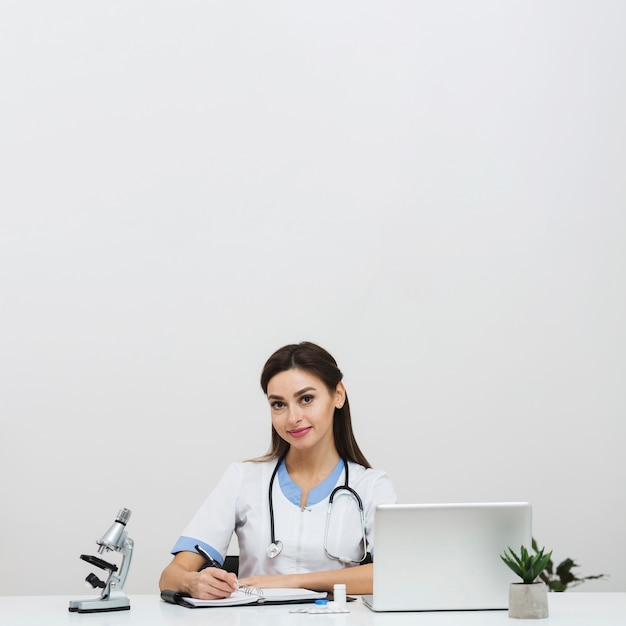 Giovane medico femmina seduta in ufficio Foto Gratuite