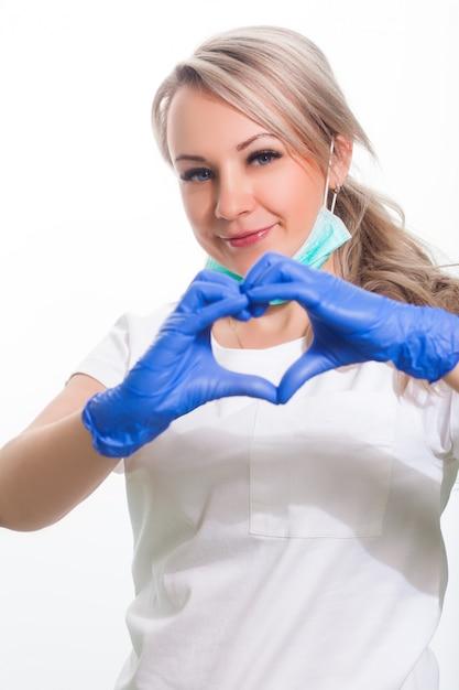 Giovane medico femminile in dentista in uniforme medica bianca e maschera sorridente e posare positivamente su sfondo bianco isolato Foto Premium