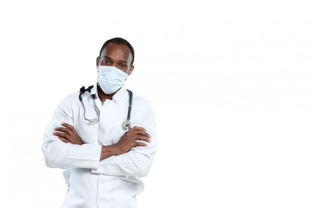 Giovane medico maschio con lo stetoscopio e la maschera di protezione isolati su bianco Foto Gratuite