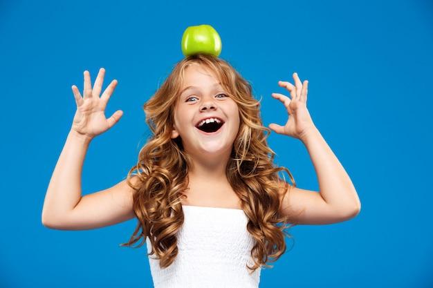 Giovane mela graziosa della tenuta della ragazza sulla testa sopra la parete blu Foto Gratuite