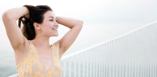 Giovane modello femminile asiatico che tiene i suoi capelli Foto Gratuite