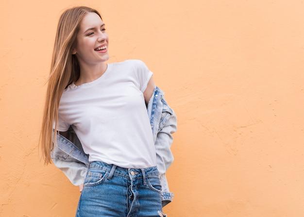 Giovane modello femminile sorridente che posa sulla parete beige strutturata Foto Gratuite