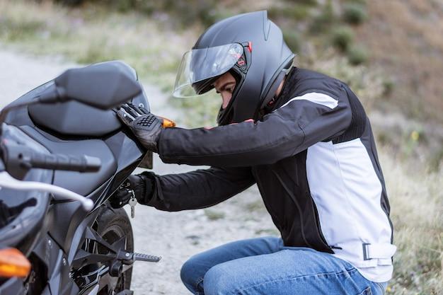 Giovane motociclista maschio che controlla la sua motocicletta prima di guidarlo Foto Premium