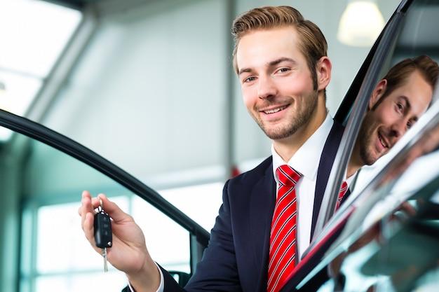 Giovane o commerciante automatico nel concessionario auto Foto Premium