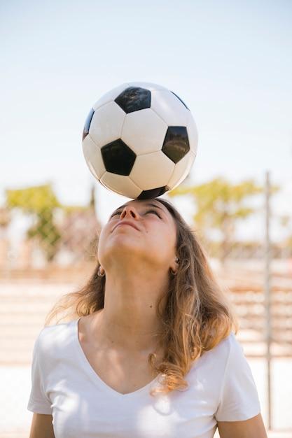 Giovane pallone da calcio d'equilibratura biondo sulla testa in stadio Foto Gratuite