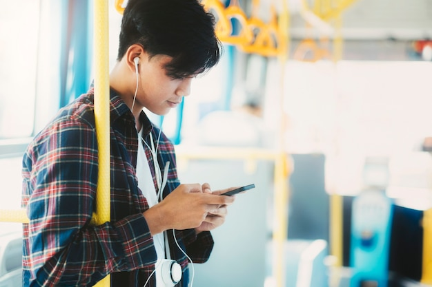 Giovane passeggero maschio asiatico che utilizza telefono cellulare sul bus pubblico. Foto Premium