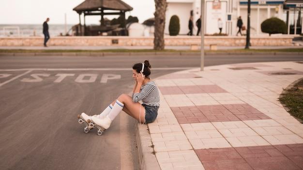 Giovane pattinatore femminile che si siede sulla musica d'ascolto del marciapiede sulla cuffia Foto Gratuite