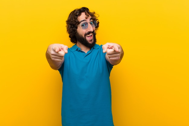 Giovane pazzo che si sente felice e fiducioso, indicando la fotocamera con entrambe le mani e ridendo, scegliendo te contro il muro arancione Foto Premium