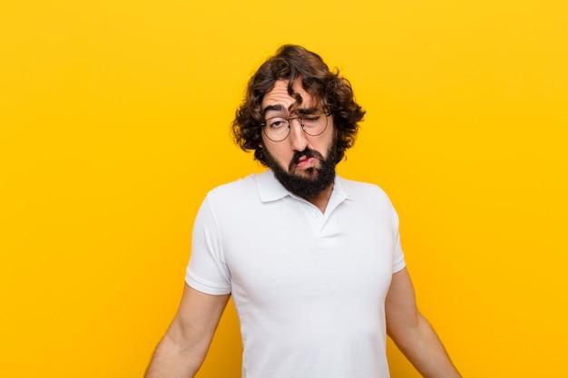 Giovane pazzo che si sente incapace e confuso, non avendo idea, assolutamente perplesso con uno sguardo stupido o sciocco muro giallo Foto Premium