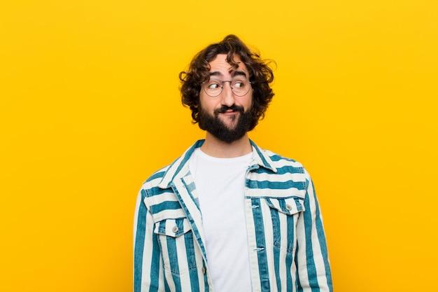 Giovane pazzo chiedendosi, pensando pensieri e idee felici, sognare ad occhi aperti, cercando di copiare lo spazio sul lato contro il muro giallo Foto Premium