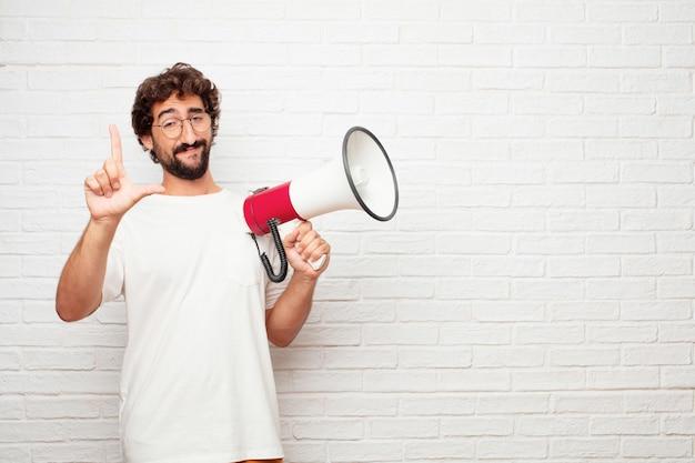 Giovane pazzo con un megafono contro il muro di mattoni. Foto Premium