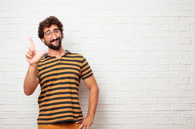 Giovane pazzo o uomo sciocco che gesturing e che esprime le emozioni contro il fondo del muro di mattoni Foto Premium