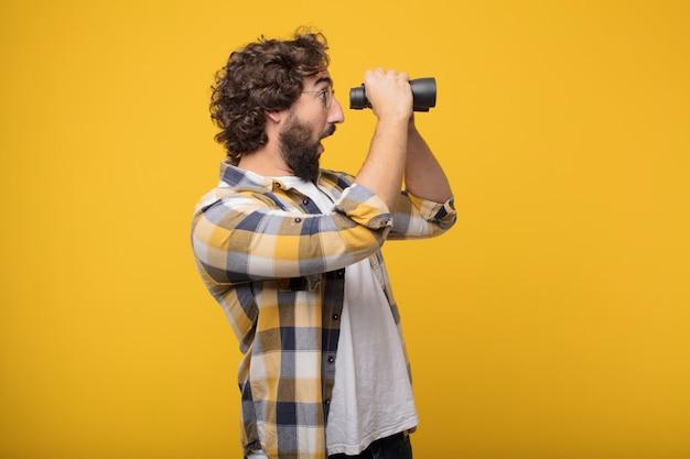 Giovane pazzo pazzo pazzo posa con un binocolo Foto Premium