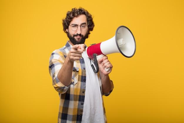 Giovane pazzo pazzo pazzo posa con un megafono. annuncio co Foto Premium