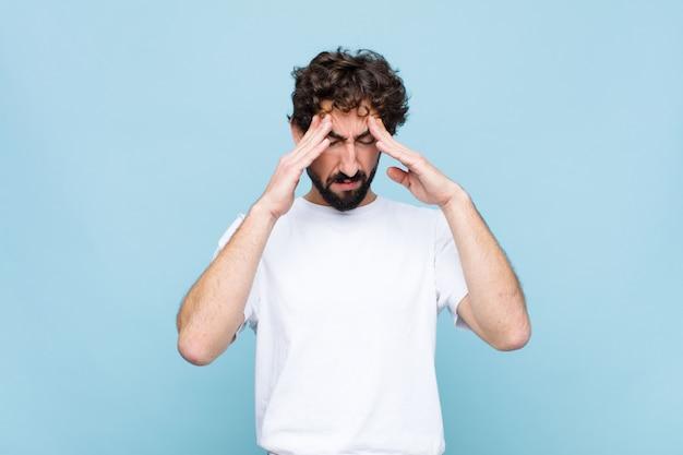 Giovane pazzo uomo barbuto che sembra stressato e frustrato, che lavora sotto pressione con un mal di testa e turbato da problemi contro il muro Foto Premium