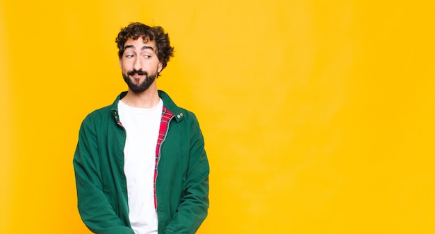 Giovane pazzo uomo barbuto che si domanda, pensando pensieri e idee felici, sognare ad occhi aperti, guardando allo spazio vuoto sul lato contro la parete piatta Foto Premium