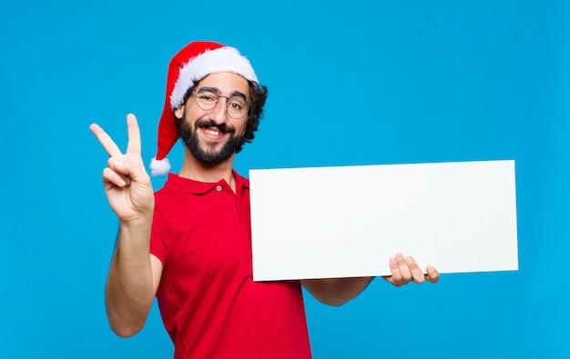 Giovane pazzo uomo barbuto con cappello santa. concetto di natale Foto Premium