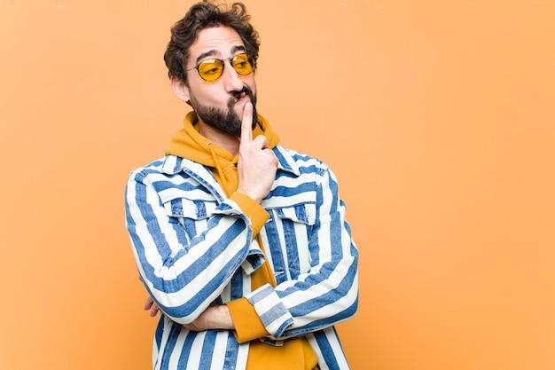 Giovane pazzo uomo freddo pensando o dubitando Foto Premium